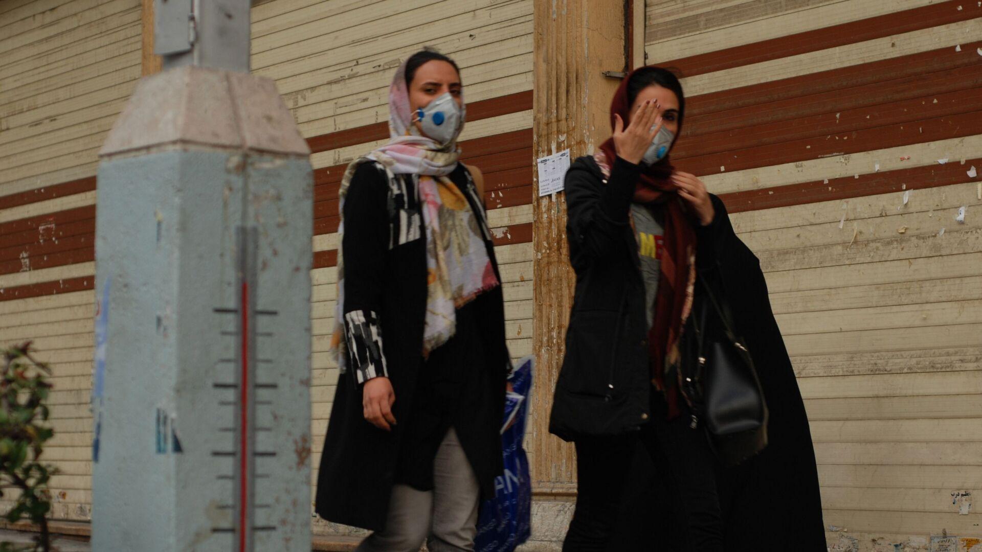 Жители Тегерана идут по одной из центральных улиц в медицинских масках - Sputnik Латвия, 1920, 15.06.2021