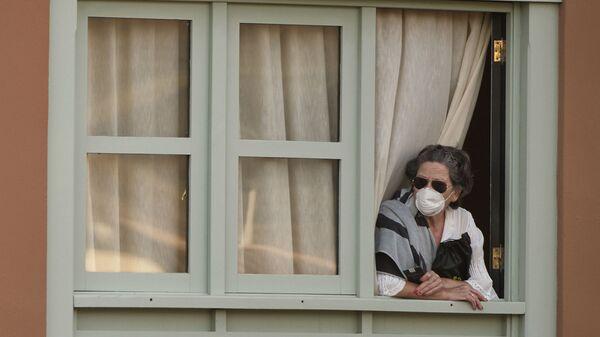 Женщина смотрит из окна Costa Adeje Palace hotel на Тенерифе - Sputnik Latvija
