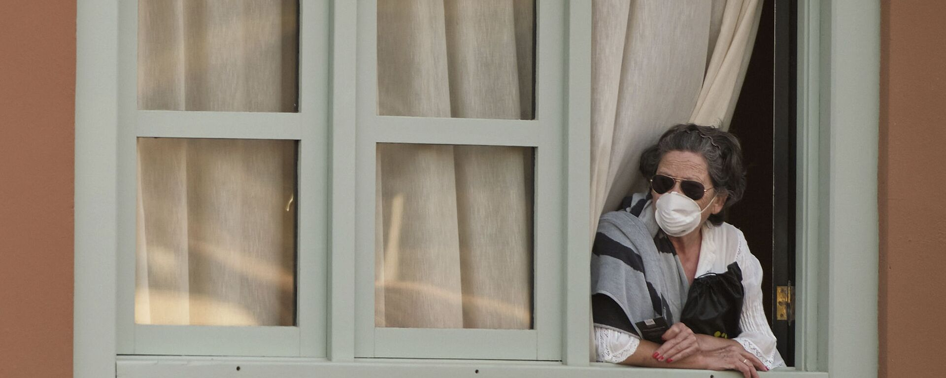 Женщина смотрит из окна Costa Adeje Palace hotel на Тенерифе - Sputnik Латвия, 1920, 03.03.2020