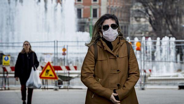 Женщина в медицинской маске в центре Милана - Sputnik Latvija