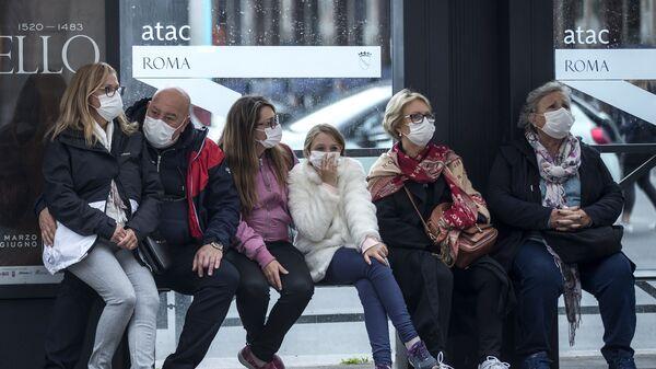 Люди в медицинских масках на автобусной остановке в Риме - Sputnik Latvija