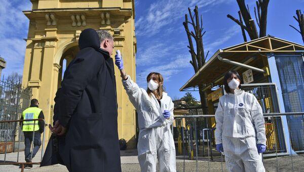 Медицинские сотрудники измеряют температуру у мужчины на улице в Парме, Италия - Sputnik Latvija
