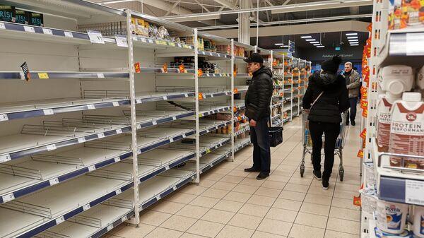 Пустые полки магазина Максима в Риге. Рижане выкупают макароны, крупы и мясные консервы - Sputnik Латвия