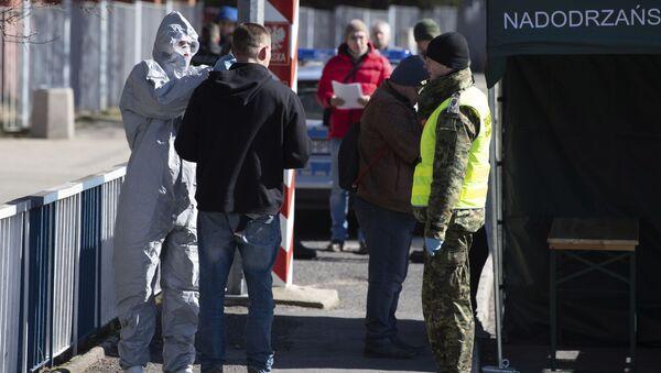 Мужчине измеряют температуру тела на пограничном пункте Згожелец, Польша - Sputnik Латвия