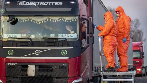 Медицинские сотрудникие осматривают пересекающих польскую границу водителей - Sputnik Латвия