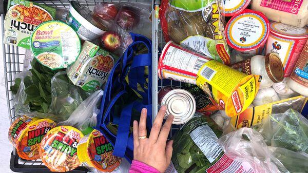 Покупатель с тележкой, наполненной продуктами в супермаркете в Канаде  - Sputnik Latvija