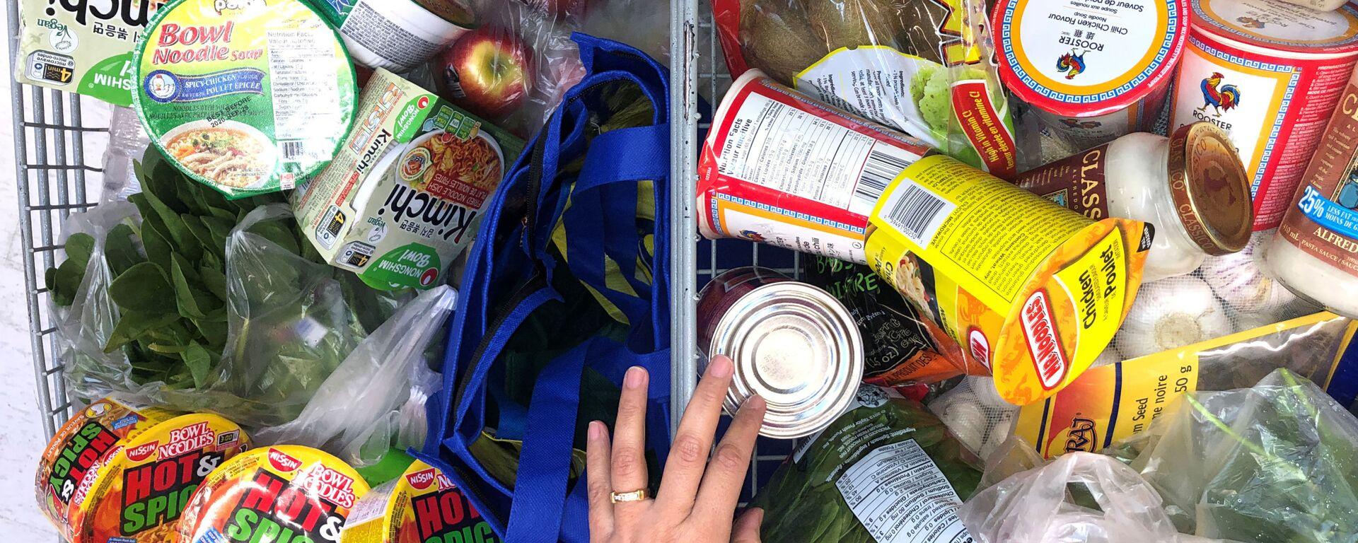 Покупатель с тележкой, наполненной продуктами в супермаркете в Канаде  - Sputnik Latvija, 1920, 01.10.2021