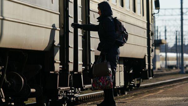 Женщина садится в вагон поезда - Sputnik Латвия