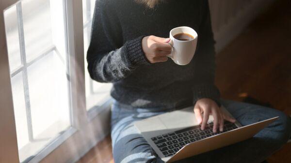 Женщина пьет кофе во время работы за ноутбуком - Sputnik Латвия