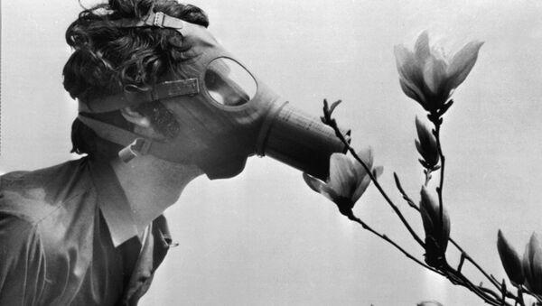 Студент в противогазе нюхает цветок в парке Нью-Йорка в 1970 году, архивное фото - Sputnik Латвия