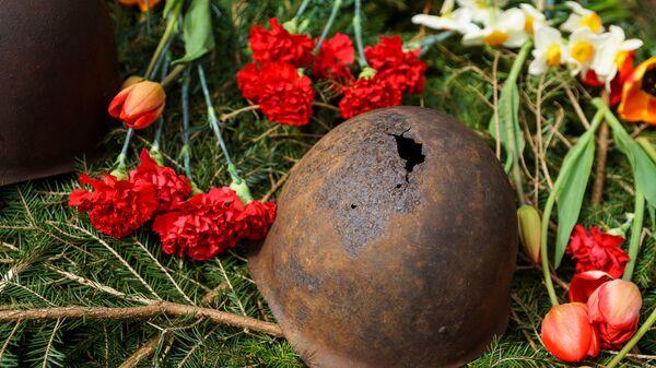 Пробитая пулей каска времен Второй мировой войны на могиле советских воинов - Sputnik Латвия