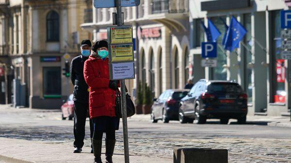 Женщина и мужчина в защитных масках на остановке общественного транспорта в Риге - Sputnik Latvija