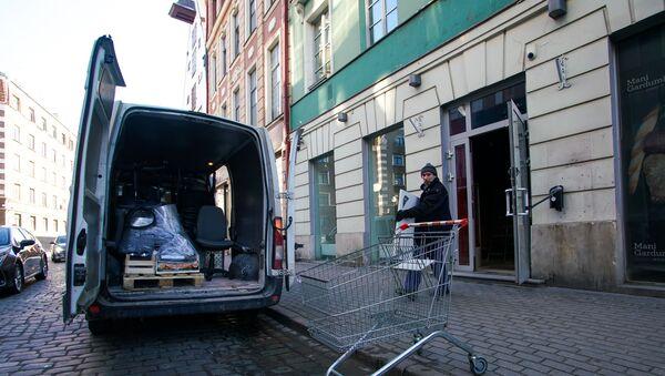 Грузчики выносят вещи из закрытого магазина в Старой Риге - Sputnik Латвия