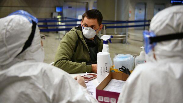 Медицинские работники во время проверки состояния пассажира в аэропорту Внуково - Sputnik Latvija