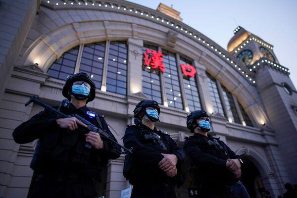 Сотрудники службы безопасности в защитных масках у железнодорожного вокзала Ханькоу в Ухане, Китай - Sputnik Латвия