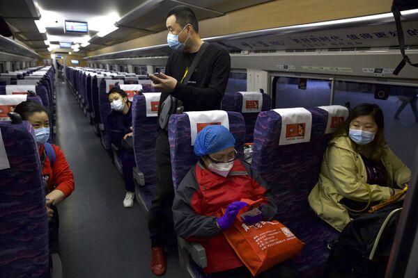 Пассажиры в защитных масках в первом поезде после возобновления движения в Ухане, Китай - Sputnik Латвия