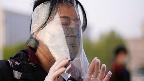 Путешественник в защитной маске на вокзале Уханя - Sputnik Latvija