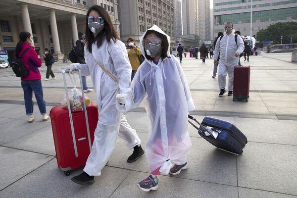 Пассажиры в защитных масках возле вокзала Уханя  - Sputnik Латвия