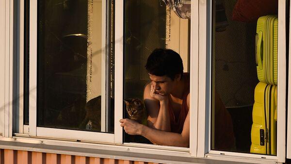 Молодой человек с кошкой на балконе многоквартирного дома в Москве - Sputnik Latvija