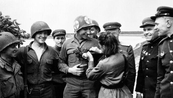 25 апреля 1945 года недалеко от города Торгау на Эльбе войска 1-го Украинского фронта встретились с войсками 1-й армии США. Советская медсестра Любовь Казиченко дарит цветы американскому солдату Карлу Робинсону. - Sputnik Latvija