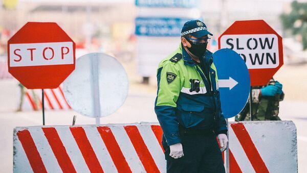 Полицейские на блокпосту во время эпидемии коронавируса проверяют автомашины - Sputnik Латвия