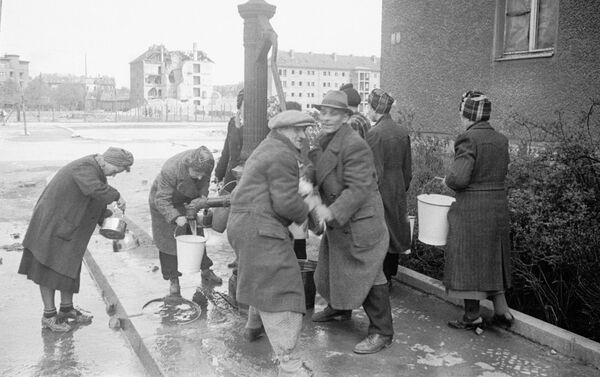 Berlīnes iedzīvotāji rindā pie ūdens sūkņa pirmajās stundās pēc pilsētas ieņemšanas - Sputnik Latvija