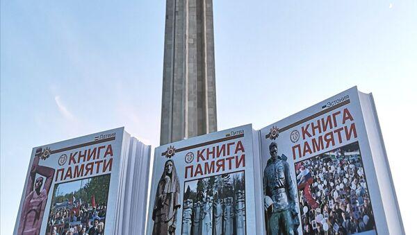 Книга памяти на фоне памятника Освободителям Риги. - Sputnik Латвия