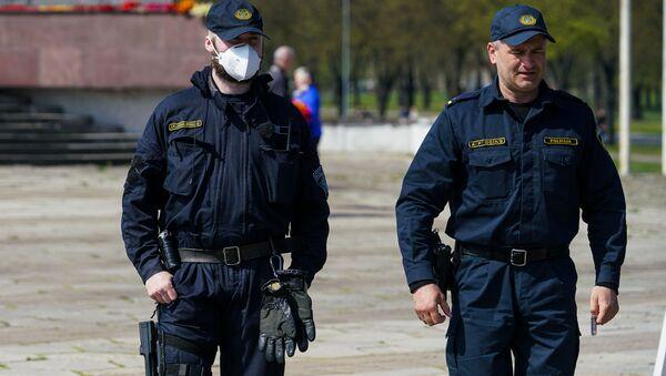 День Победы у памятника Освободителям в Риге. Полицейский в маске - Sputnik Latvija