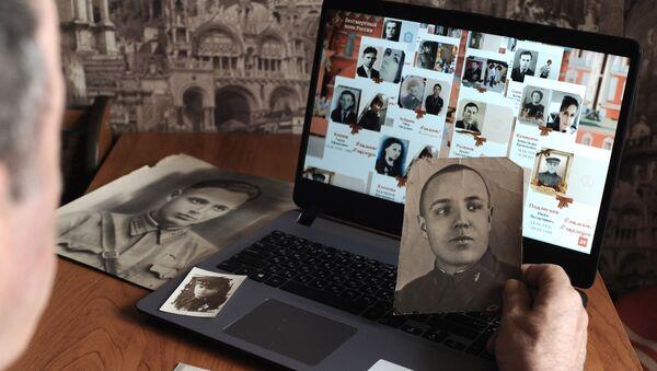 Мужчина смотрит онлайн-трансляцию акции Бессмертный полк - Sputnik Латвия