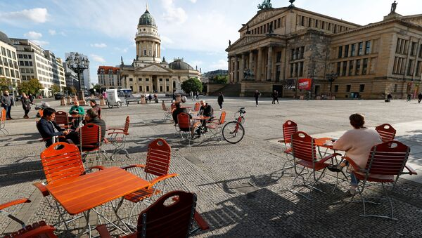 Люди наслаждаются погодой в кафе на площади Жандарменмаркт в Берлине, соблюдая принцип социальной дистанции - Sputnik Latvija