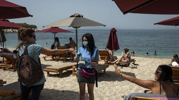 Отдыхающие во время аренды шезлонгов на пляже в Греции   - Sputnik Latvija