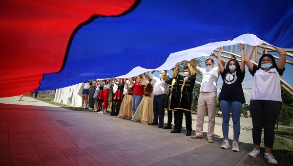 Участники празднований Дня России держат российский флаг в парке Дружбы города Георгиевска Ставропольского края - Sputnik Латвия