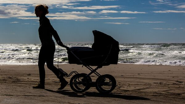 Девушка с детской коляской на берегу моря - Sputnik Latvija