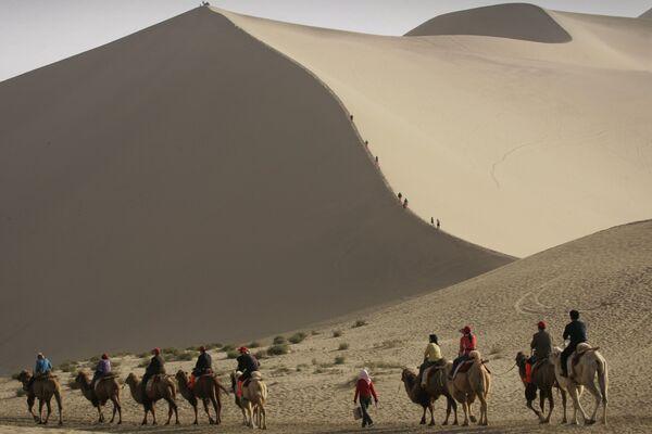 Туристы катаются на верблюдах на краю пустыни, которая угрожает поглотить древний китайский город Дуньхуан  - Sputnik Латвия
