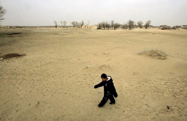 Ребенок идет по песчаной дюне в Вайси, китайская провинция Ганьсу, где нерациональное земледелие привело к опустыниванию - Sputnik Латвия