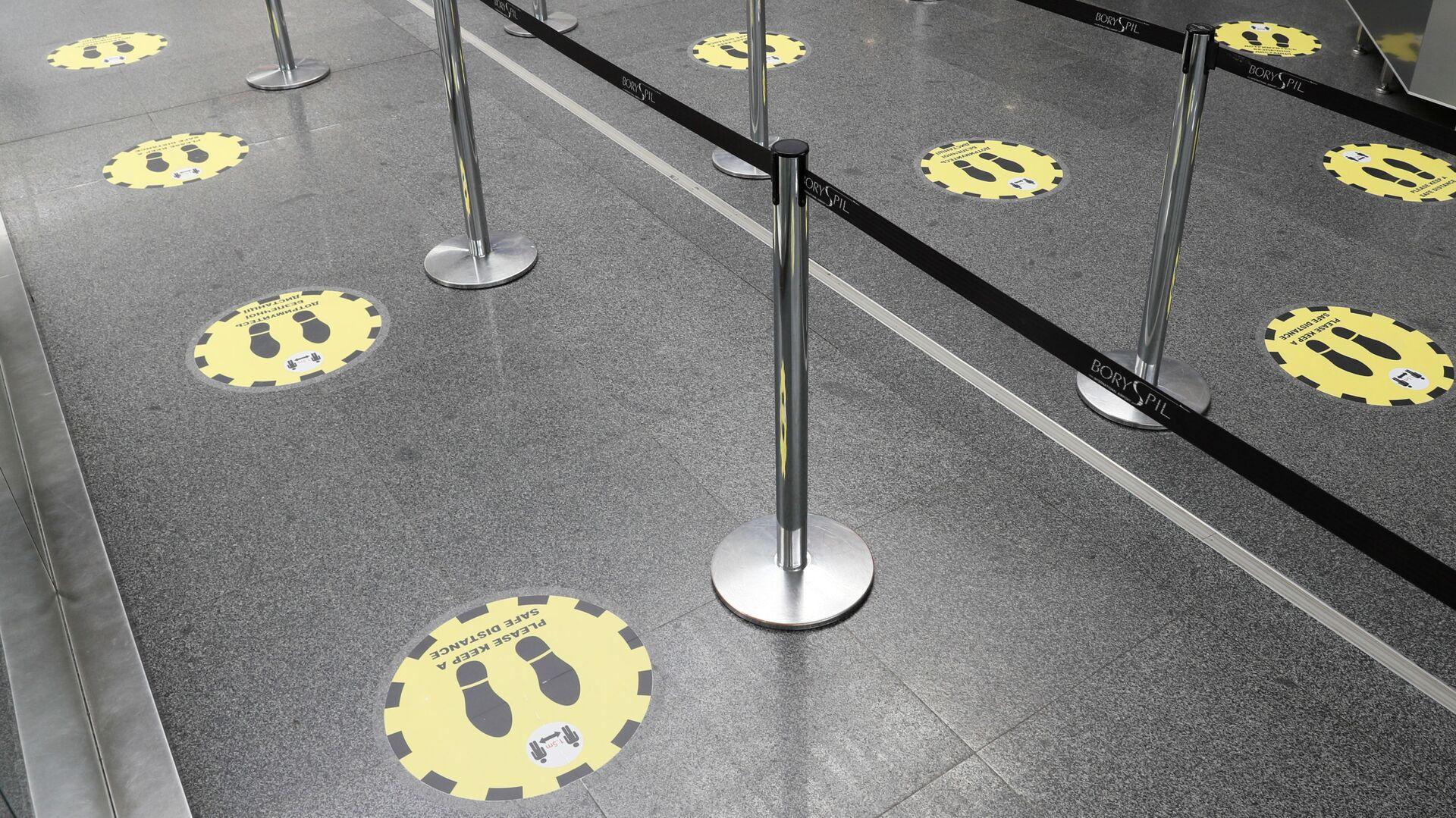 Отметки о необходимости соблюдать социальную дистанцию в международном аэропорту Борисполь в Киеве - Sputnik Latvija, 1920, 12.10.2021