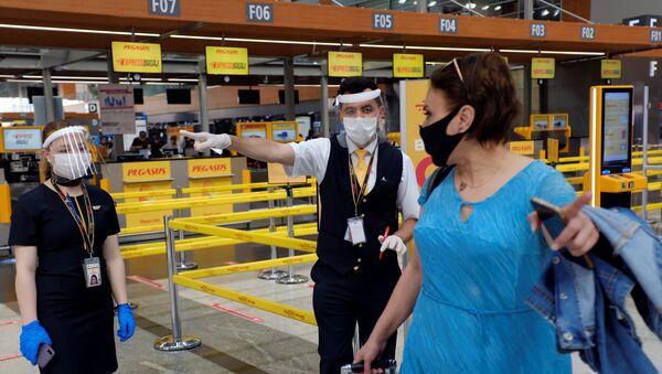 Сотрудники авиакомпании Pegasus Airlines в защитных масках и экранах указывают пассажиру нужное направление в международном аэропорту имени Сабихи Гекчен в Стамбуле - Sputnik Latvija