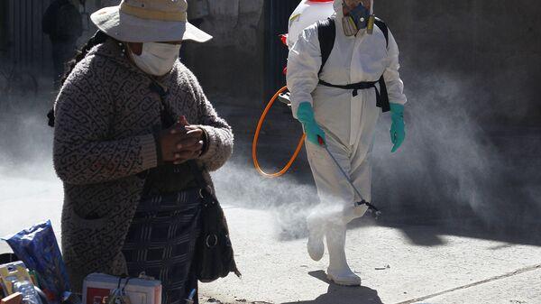 Муниципальный работник во время дезинфекции улиц в Пуно, Перу - Sputnik Latvija