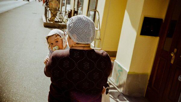 Ребенок на руках у женщины - Sputnik Латвия