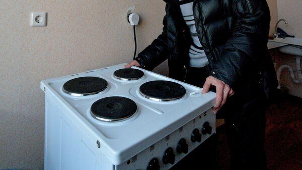Мужчина осматривает электрическую плиту. Архивное фото - Sputnik Латвия