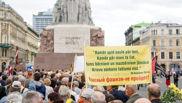 Надпись на плакате - Пока тебе светит солнце, пока мне льёт дождик. Нам нужно учить наших детей и внуков, русский красный фашизм не пройдёт - Sputnik Latvija