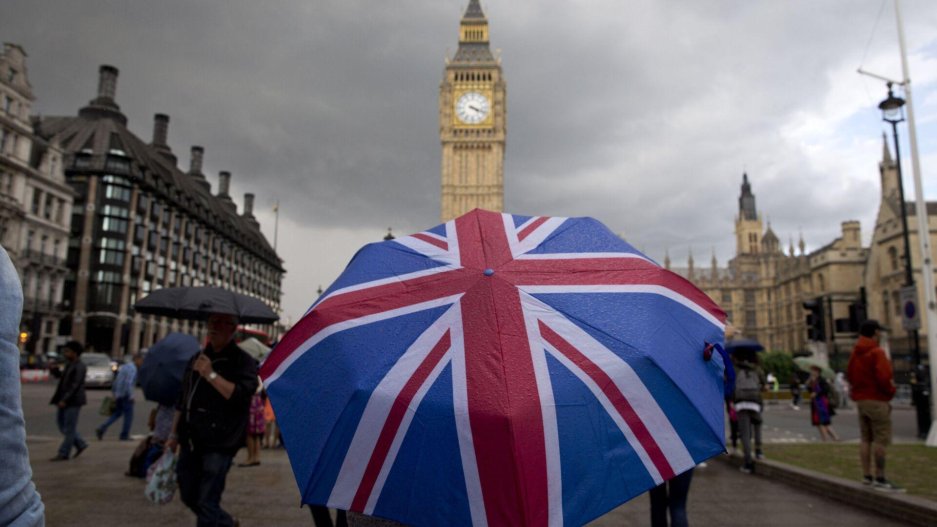 Пешеход с зонтом в цветах британского флага в Лондоне - Sputnik Латвия, 1920, 26.09.2021