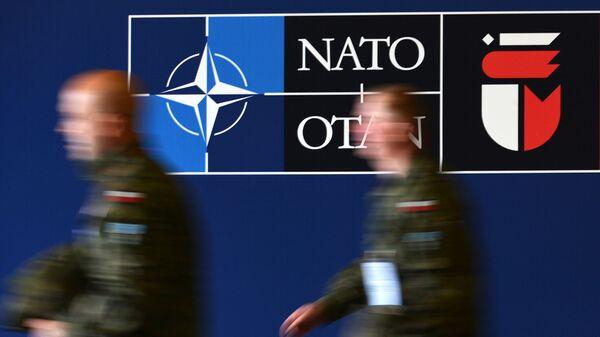 Мужчины у баннера саммита НАТО на Национальном стадионе в Варшаве - Sputnik Латвия