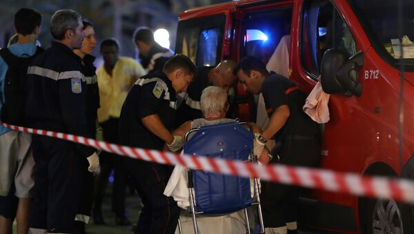 Rescue workers help an injured woman to get in a ambulance on July 15, 2016, after a truck drove into a crowd watching a fireworks display in the French Riviera town of Nice. - Sputnik Latvija