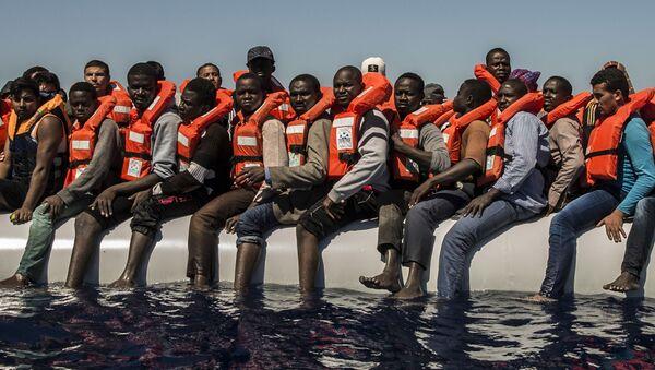 Беженцы ждут спасательную шлюпку в Средиземном море - Sputnik Latvija