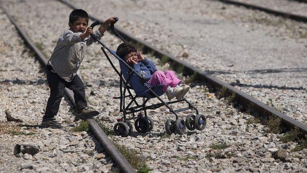 Мальчик везет коляску с ребенком в лагере беженцев в Идомени, Греция - Sputnik Латвия