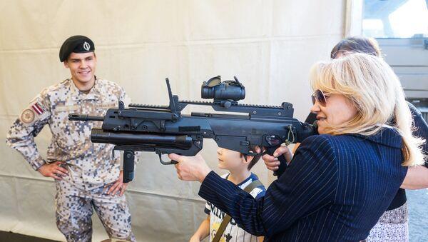 Rīgas iedzīvotāja ar Latvijas Bruņoto spēku standarta šauteni Heckler-Koch G36 - Sputnik Latvija