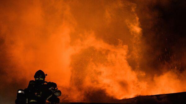 Архивное фото сотрудника пожарно-спасательного подразделения МЧС на тушении возгорания - Sputnik Латвия