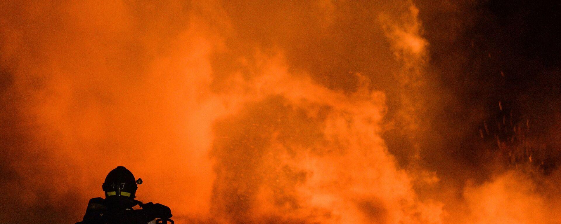 Архивное фото сотрудника пожарно-спасательного подразделения МЧС на тушении возгорания - Sputnik Латвия, 1920, 03.07.2021