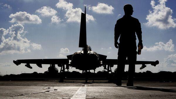Британский солдат рядом с самолетом Typhoon на авиабазе Акротири, недалеко от Южного прибрежного города Лимассол на Кипре - Sputnik Латвия